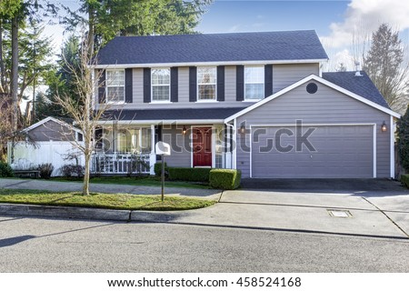 Blue gray house exterior with french windows and red entrance door. Also garage with concrete driveway. Northwest, USA