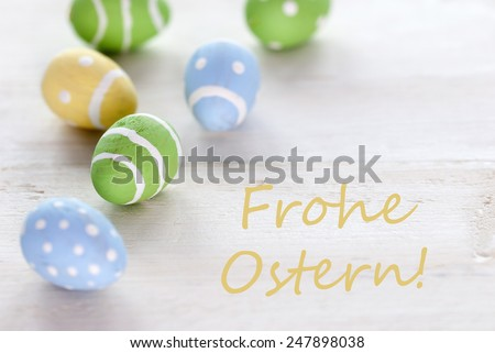 Blue Green And Yellow Easter Eggs Which Are Dotted And Striped On Wooden Vintage Background With German Text Frohe Ostern Which Means Happy Easter For Easter Greetings - stock photo