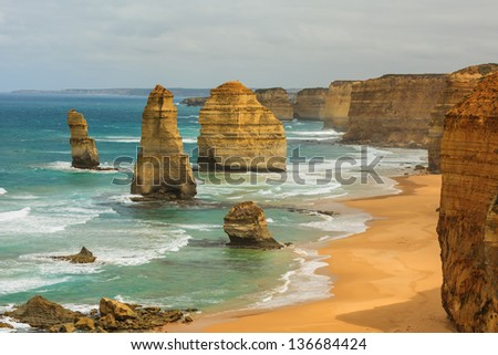 Blue green ocean and beach with sandbanks cliffs and waves  with close view of The twelve apostles and cliffs in the shadow of the late afternoon sun in Victoria, Australia against a blue cloudy sky - stock photo