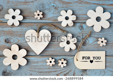 blue grey background with wooden hearts and flower and with love, for you label - stock photo