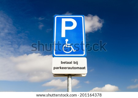 Blue handicapped parking sign for disabled drivers against a dramatic sky