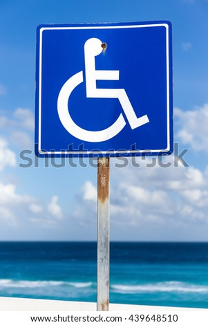 Blue handicapped sign with wheelchair, outdoors on blue sky background