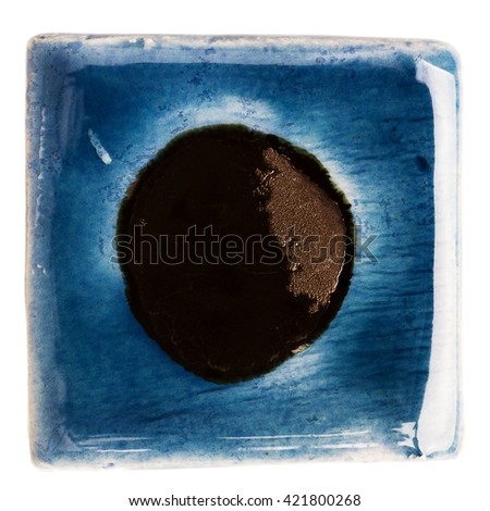 Blue handmade glazed ceramic tile with big black dot in middle isolated on white - stock photo