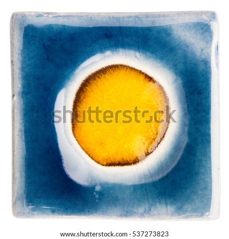 Blue handmade glazed ceramic tile with big orange dot in middle isolated on white