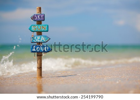 """Blue handmade signpost made of wood and bamboo with the inscription """"sky, sun, sea, love"""" on the tropical beach in Thailand. Space for text. - stock photo"""