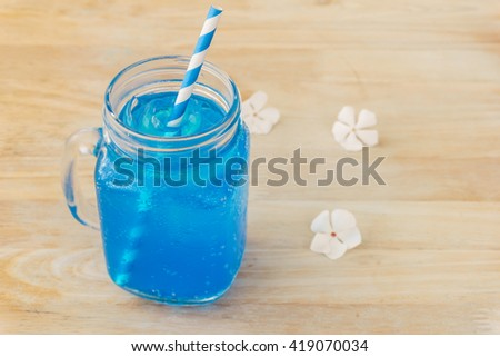 Blue Hawaiian lime soda on wooden table.