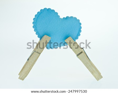 Blue heart with a clothespin on white background - stock photo