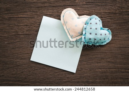 Blue hearts handmade crafts from polka dot cotton cloth with blank notepad place on wood background with vignette, wedding and anniversary symbol - stock photo