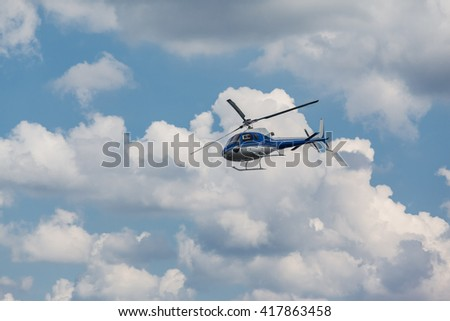 Blue helicopter flies in the clouds