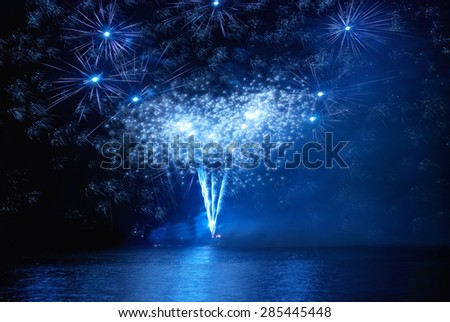 Blue holiday fireworks on the black sky background - stock photo