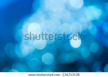 Blue holiday party background. Abstract with bright twinkles, sparkles, blurred, defocused light. - stock photo