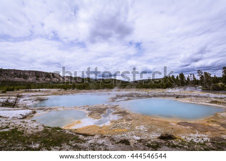 Blue hot springs with pine trees and blue cloudy sky in Midway Geyser Basin, Yellowstone National Park - stock photo