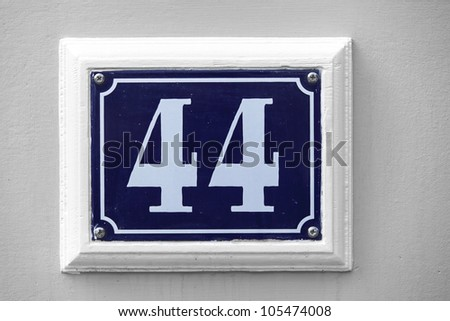 Blue house number tile plaque with floral ornament. - stock photo