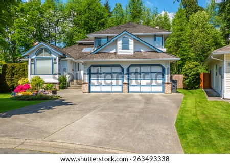 Blue house with beautiful landscaping on a sunny day. Home exterior. - stock photo