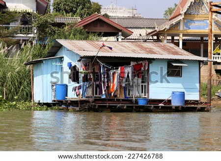 blue house with the laundry in the river in Thailand   - stock photo