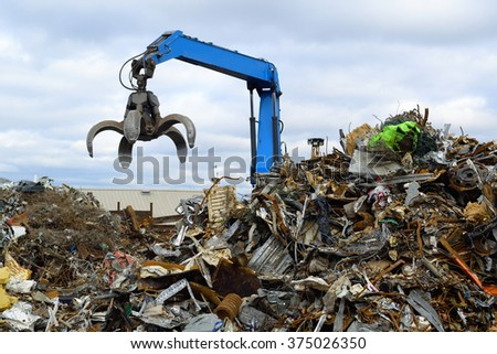 Blue hydraulic Clow Crane used for picking up scrap metal at recycling yard - stock photo