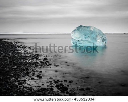 Blue Iceberg in the Sea, at the black Beach of Iceland - stock photo