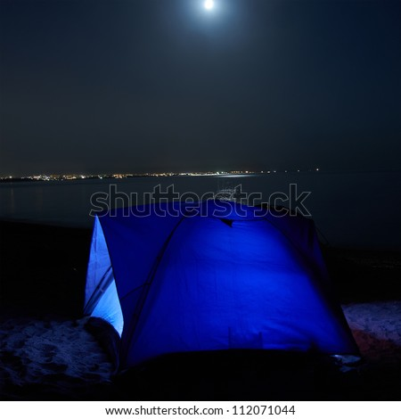 Blue illuminated tent at night on the beach. Moon, stars and reflection in water - stock photo