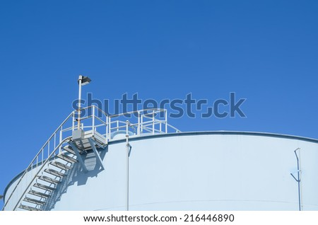 Blue industrial storage tank against cloudless blue sky - stock photo