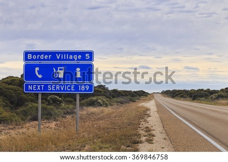 blue informational road sign in Western Australia about next service as well as perspective of Eyre Highway towards Border Village - stock photo