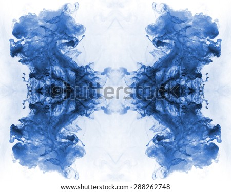 Blue ink forming patterns resembling Rorschach Test ink blots. - stock photo