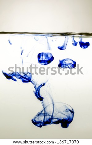 Blue ink in colored water on white background.