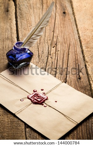 Blue ink inkwell with feather on envelope with red sealant - stock photo
