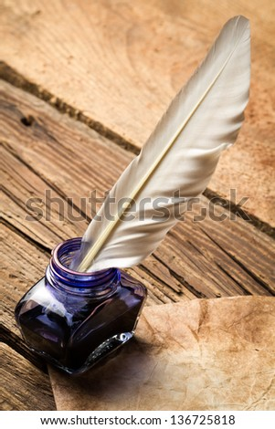 Blue ink with feather on old vintage letter - stock photo