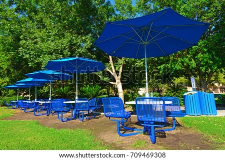 Blue is the theme of this outdoor eating area including tables, chairs and umbrellas.