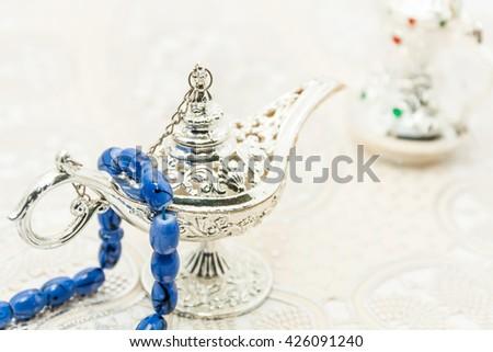 Blue islamic prayer-beeds on silver alaadin's lamp. Ramadan , Eid background concept - stock photo
