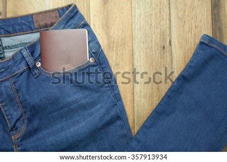 Blue jeans and passport with wooden background - stock photo