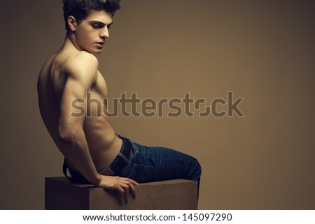 Blue jeans concept. Handsome muscular male model in blue jeans with perfect muscular body posing over wooden background, sitting on a wooden cube. Vogue style. Copy-space. Fashion studio portrait - stock photo