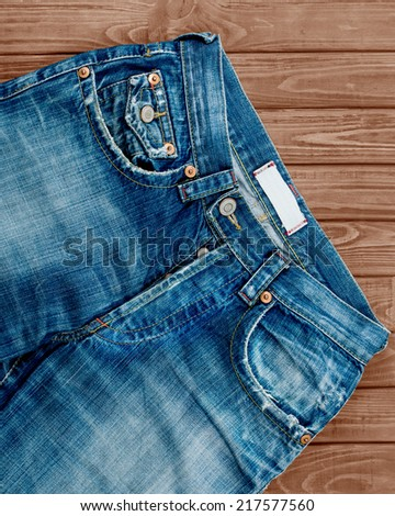 Blue jeans on the wood background - stock photo