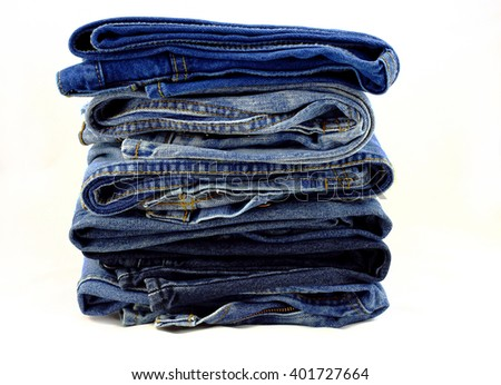 Blue jeans pants pile on a white background. - stock photo