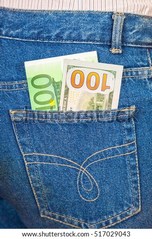 Blue jeans pocket with one hundred euro and one hundred american dollar