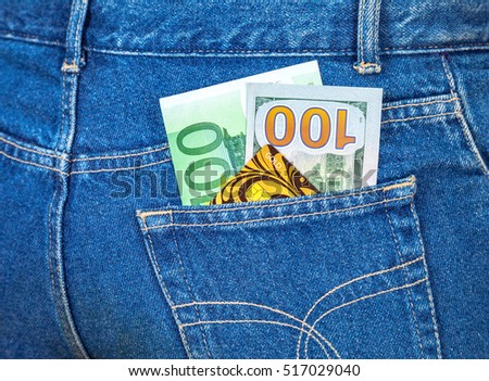 Blue jeans pocket with one hundred euro, one hundred american dollar and credit card
