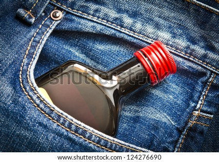 Blue jeans pocket with small bottle of alcohol - stock photo