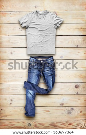 BLue jeans trouser and shirt over wood background - stock photo