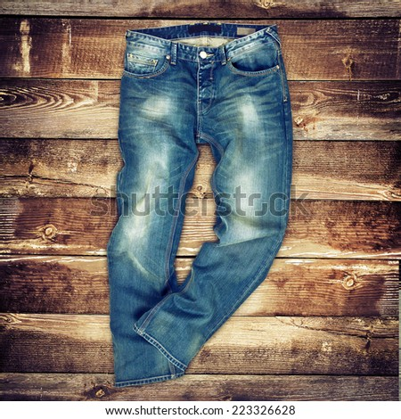 Blue jeans trouser over brown wood planks background - stock photo