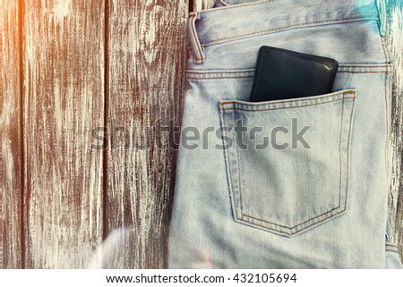 Blue jeans with a wallet in the pocket on the background of vintage boards. Lens flare effect - stock photo