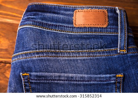 blue jeans with half of back pocket and brown leather tag on wood table background.  - stock photo