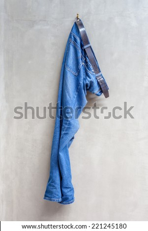 Blue jeans with leather belt is hanging on hanger with exposed concrete wall in bathroom. - stock photo