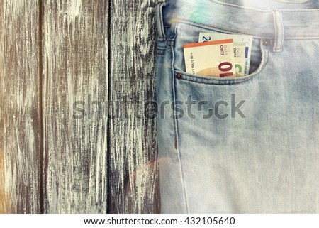 Blue jeans with money in the pocket on the background of vintage boards. Lens flare effect - stock photo