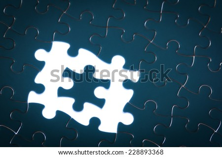 blue jigsaw puzzle with missing pieces with light glow concept of incomplete challenge - stock photo