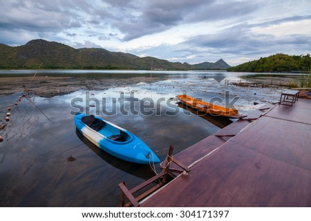 Blue kayak and orange boat mooring at the wooden deck during twilight in a lake, reflection of sky on still water