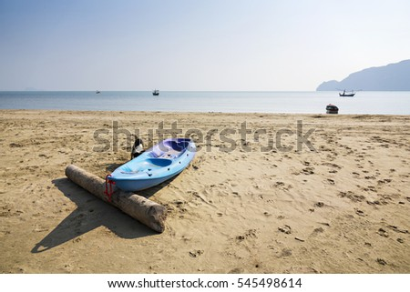 Blue Kayak on sand beach in day light