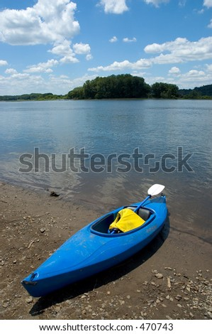 Blue kayak sitting on the bank of a river.
