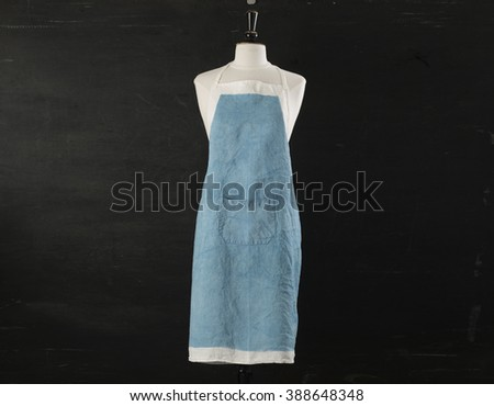 Blue kitchen apron with pocket on mannequin over a black backdrop.