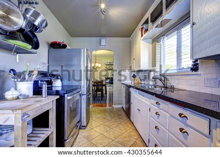 Blue kitchen interior with brown tile, stainless steel refrigerator and white cabinets - stock photo