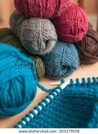 Blue knit work on needles with yarn balls in the background - stock photo